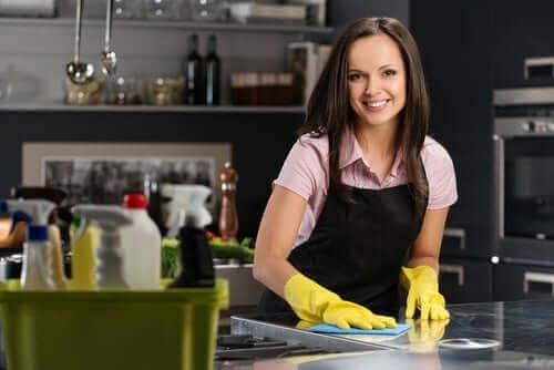 En kvinne som rengjør kjøkkenbenken.