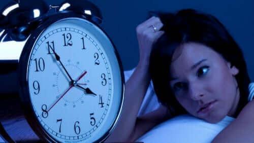 En kvinne som stirrer på klokken sin, ikke i stand til å sove.
