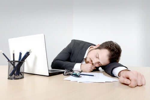 En mann som har sovnet på skrivebordet sitt.