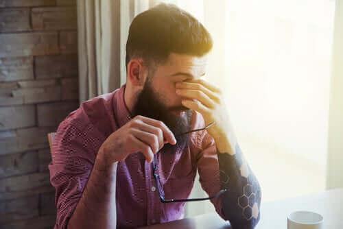De forskjellige typene søvnløshet: En søvnig mann som gnir seg i øynene.