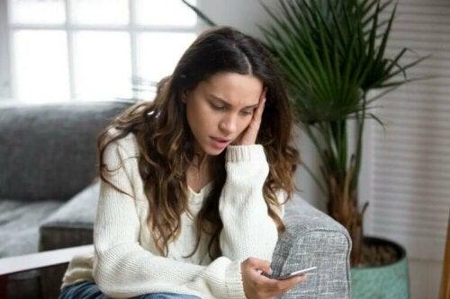 En bekymret kvinne med telefonen sin
