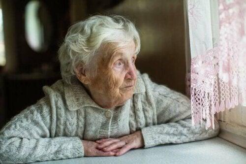 Eldre kvinne sitter ved vinduet
