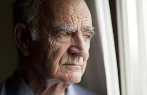 Eldre mann ser ut av vinduet