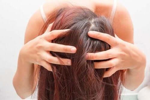 En kvinne atår bøyd med hendene i håret