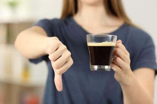 En kvinne med en kaffekopp og tommelen ned.