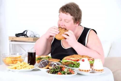En overvektig kvinne som spiser masse unsunn mat.