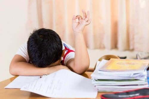 En sliten gutt med hodet på pulten.
