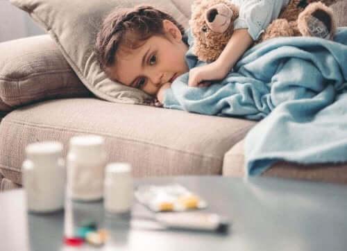 Et barn som ligger på sofaen med en bamse.