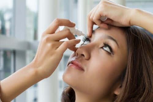 Hvordan bruke oftalmisk oksymetazolin En kvinne som tar dråper i øynene.
