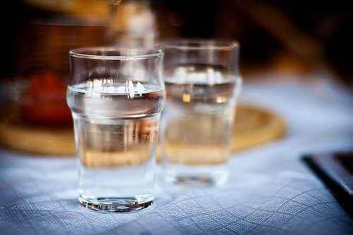 To glass vann som står på et bord.