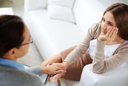 Kvinne holder hender med en terapeut