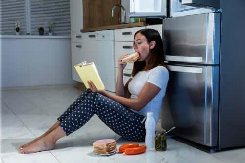 Kvinne sitter foran kjøleskapet og spiser