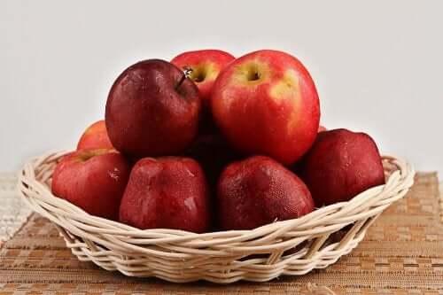 En kurv som er fylt med røde epler