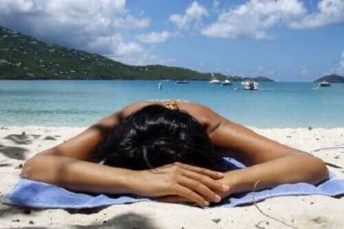 En kvinne som soler seg på en strand