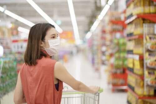En kvinne med en maske i dagligvarebutikken