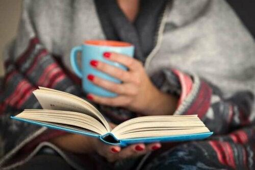 En kvinne leser en bok og drikker varm drikke: prøv det for å ta vare på den mentale helsa di