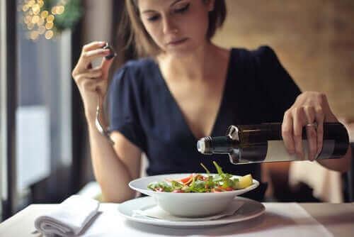 En kvinne som tilsetter olivenolje i en salat.