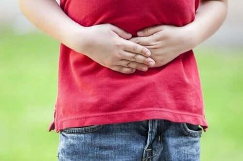 Et barn som holder seg på magen.