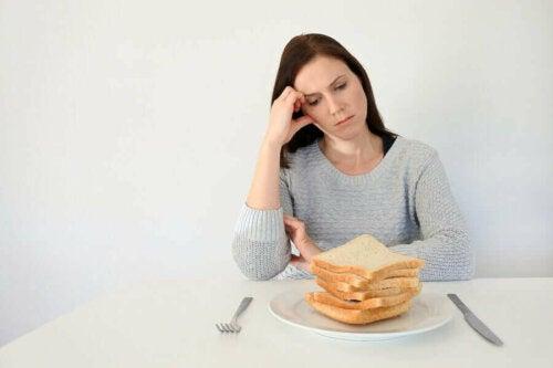 En kvinne som sitter ved en tallerken med loffskiver