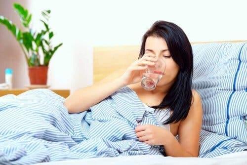En kvinne i sengen som drikker vann