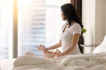 En kvinne som mediterer på rommet sitt.