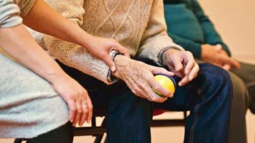 En kvinne som holder hånden til en eldre mann