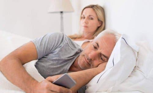 En mann på mobilen i sengen med kjæresten ved siden av seg