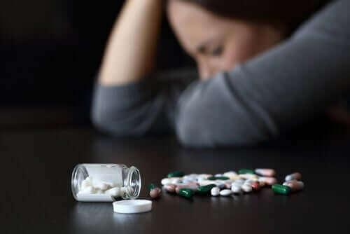 En trøtt kvinne og medisiner på et bord