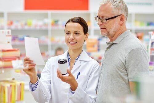 En farmasøyt som forteller en mann hvordan han skal lese medisinske pakningsvedlegg.