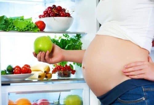 En gravid kvinne som holder et eple.