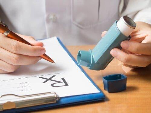 En kvinne som holder en inhalator som inneholder medikamentet ipratropiumbromid.