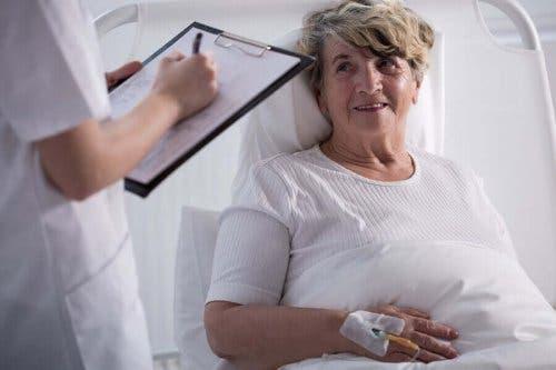 En lege som snakker med en pasient i sengen.