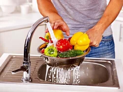 En mann som vasker grønnsaker.