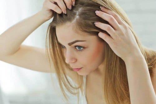 En kvinne som undersøker hårrøttene sine