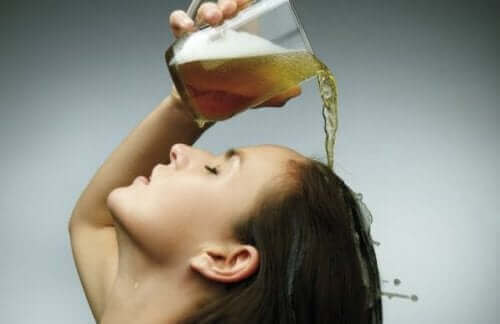En kvinne som heller øl i håret sitt