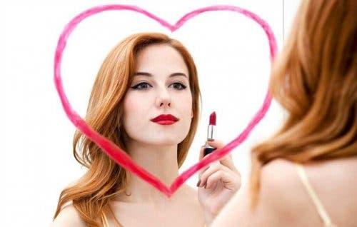 Kvinne som ser seg i speilet.