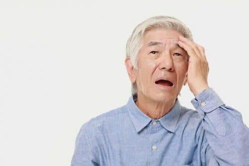 En eldre mann som tar seg på pannen