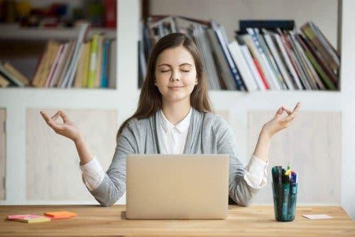 En kvinne som mediterer foran en laptop