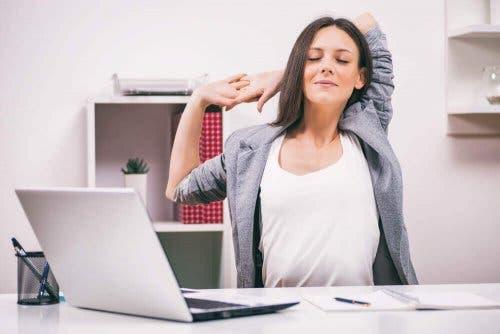 En kvinne som strekker seg foran en laptop