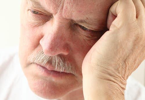 En trøtt mann lener seg på hånden sin