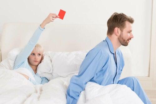 En kvinne holder et rødt kort i senga