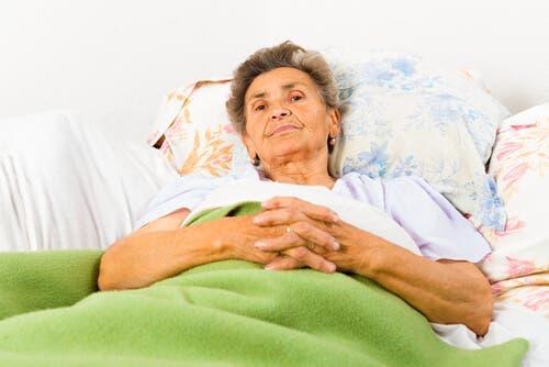 En kvinne med alzheimers ligger i sengen