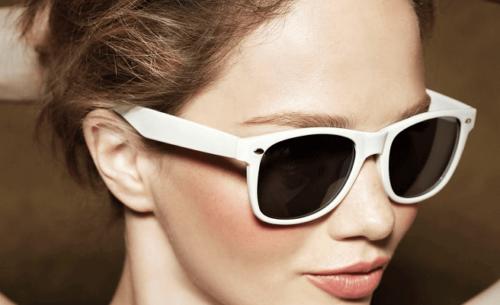 Denne kvinnen har på seg solbriller som er hvite.