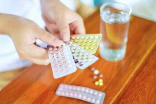 En kvinne holder forskjelige p-piller i hendene.