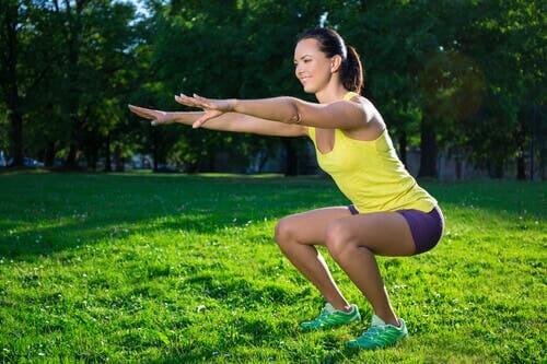 En kvinne som gjør knebøyøvelser i en park