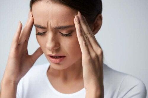 En kvinne som lider av hodepine.