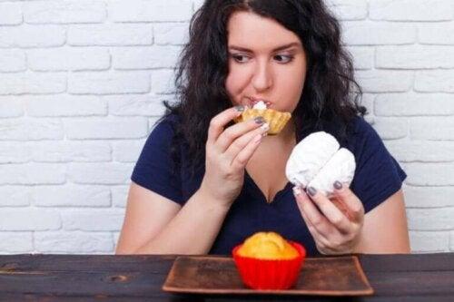 Kvinne som spiser overstadig av søtsaker.