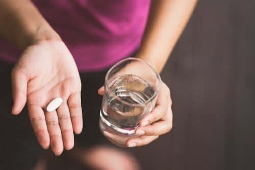 Kvinne som tar paracetamol med vann.