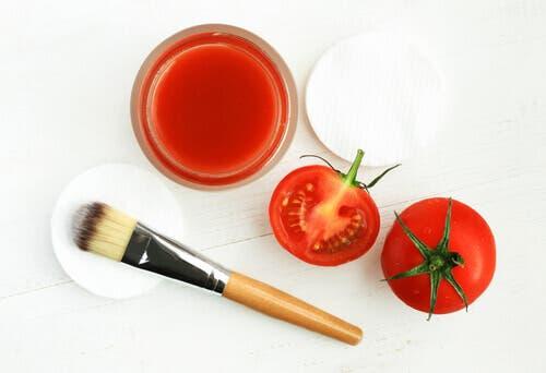 Tomater og tomatjuice på et bord sammen med en sminkebørste