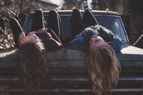 to gode venner som ligger på en gammel bil